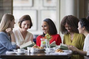 women-friends-discussing-book-club-book-at-restaurant